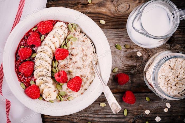 Healthy breakfast: oatmeal with fresh raspberries, banana, flax seeds and pumpkin seeds