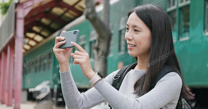 Woman traveler using smart phone for taking photo and video