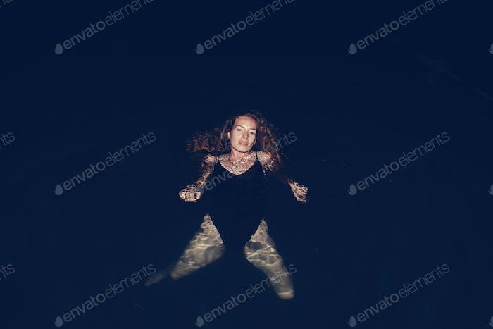 Frau schwimmen im Dunkeln