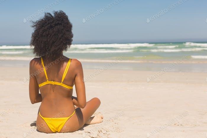 Woman in yellow bikini sitting on the beach in the sunshine