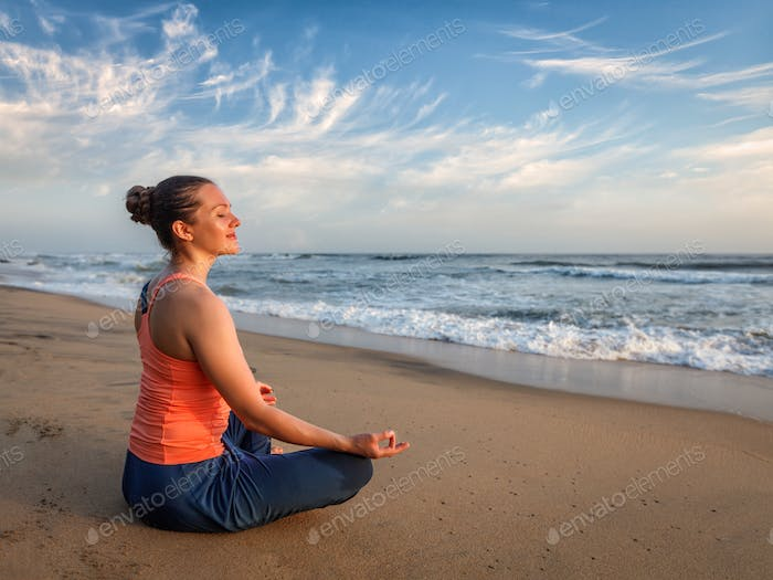 Young sporty fit woman doing yoga oudoors at beach