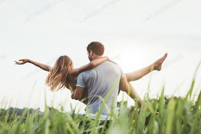 Man carrying woman in rural field
