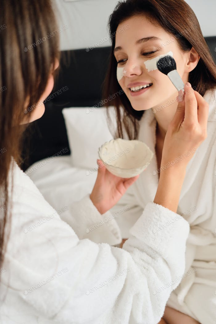 Woman in bathrobe sitting on bed dreamily looking aside while pretty girl near making cosmetic mask
