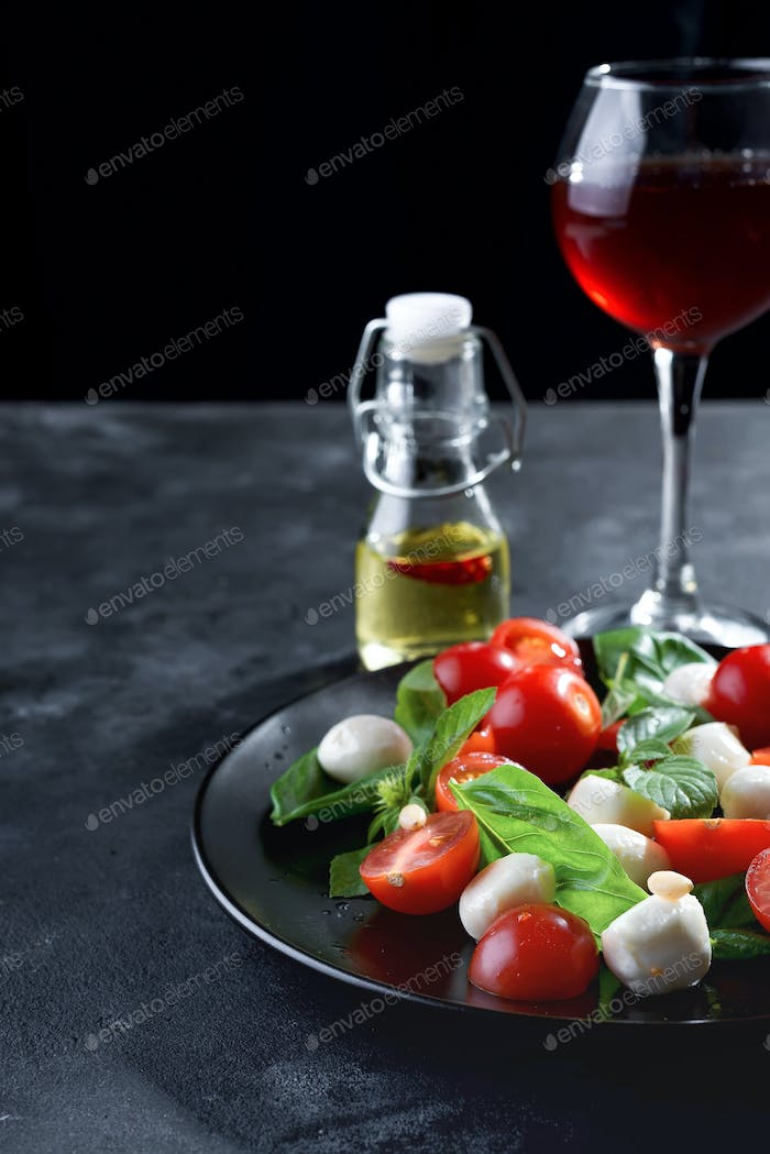 Caprese salad. Healthy meal with cherry tomatoes, mozzarella balls, spices with wine