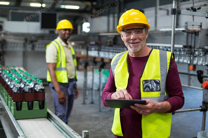 Smiling factory worker with digital tablet standing near the production line