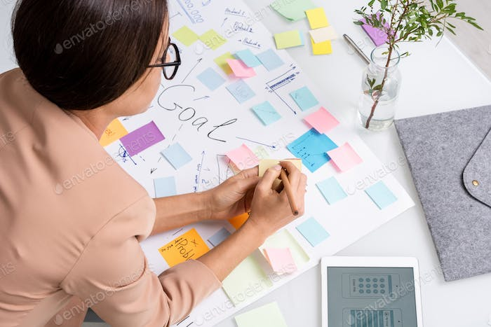 Young brunette businesswoman making notes on notepaper over large document