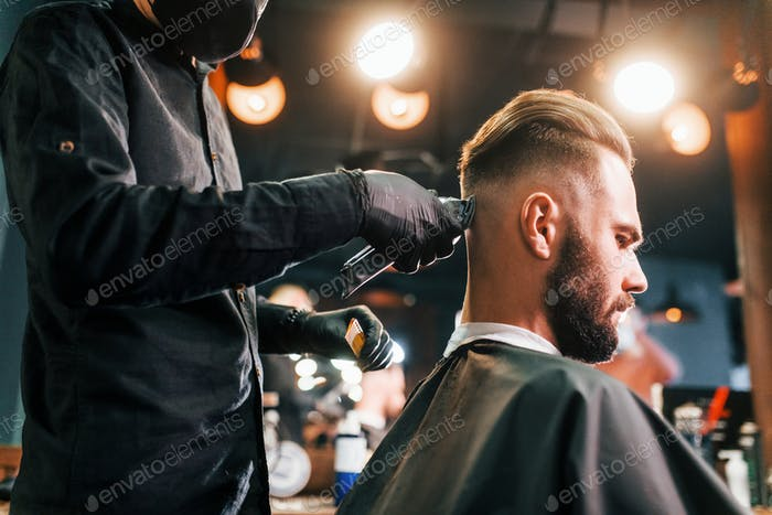 Young bearded man sitting and getting haircut in barber shop by guy in black protective mask