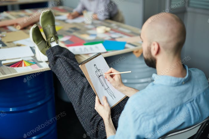 Bald man working on fashion sketch