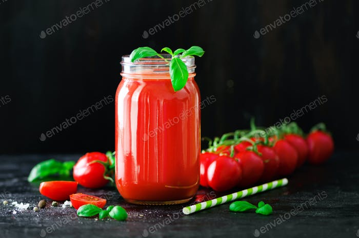 Organic fresh tomato juice in a glass jar, basil, cherry, salt, pepper and straw on dark black