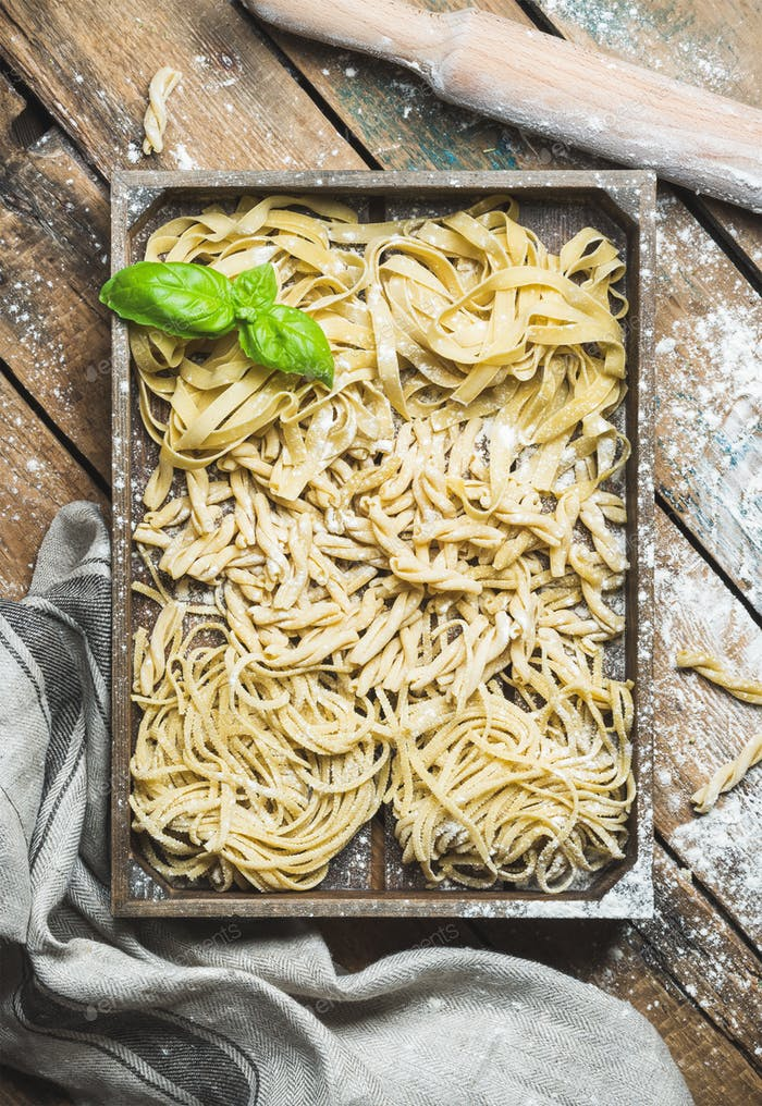Uncooked Italian pasta in wooden tray over shabby background