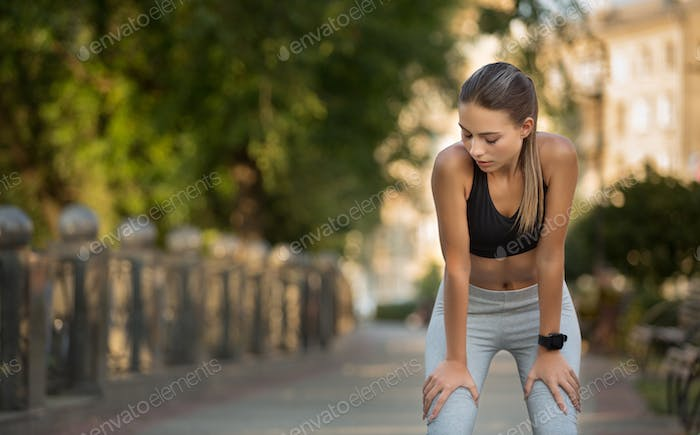 Tired woman runner taking rest after running hard