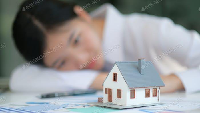 Front Modell Haus mit Mädchen im Hintergrund schauen zu Hause.Sie träumte von Haus zu kaufen.