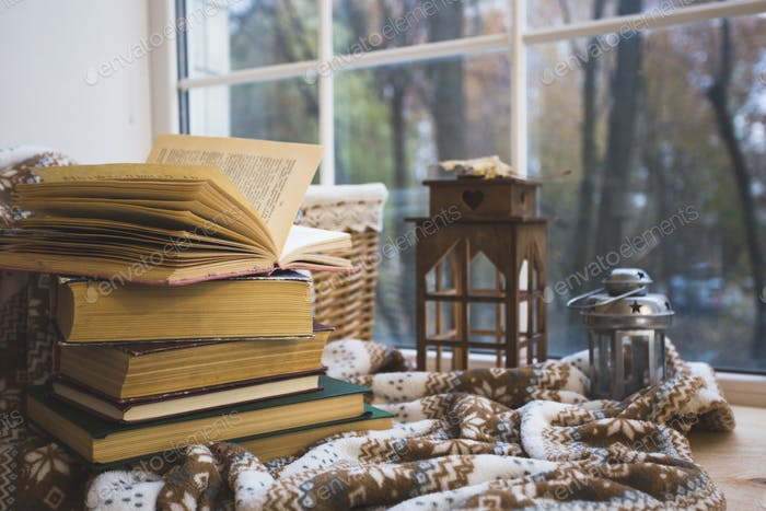 Stack of books with a warm blanket on a windowsill