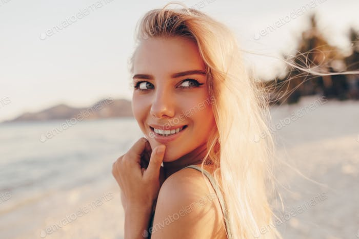 Happy  blond woman with perfect smile having fun on sunny beach, looking at camera,