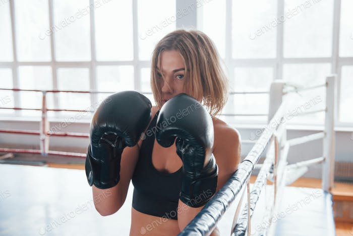 Defending from the punch. Female sportswoman training in the boxing ring. In black colored clothes