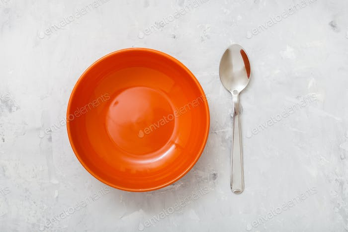 top view orange bowl and spoon on concrete plate