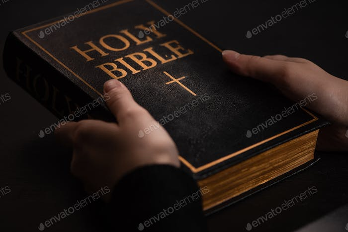 Cropped View of Woman Holding Holy Bible in Dark