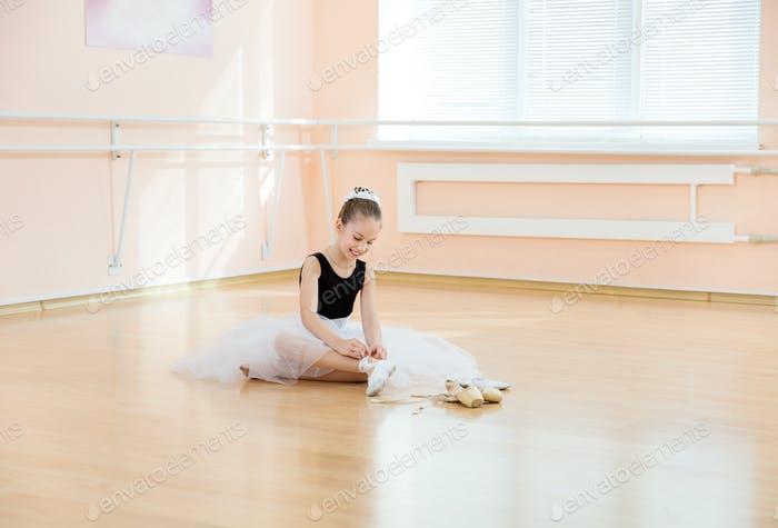 Balerina changing dancing shoes to pointe ones while sitting on floor