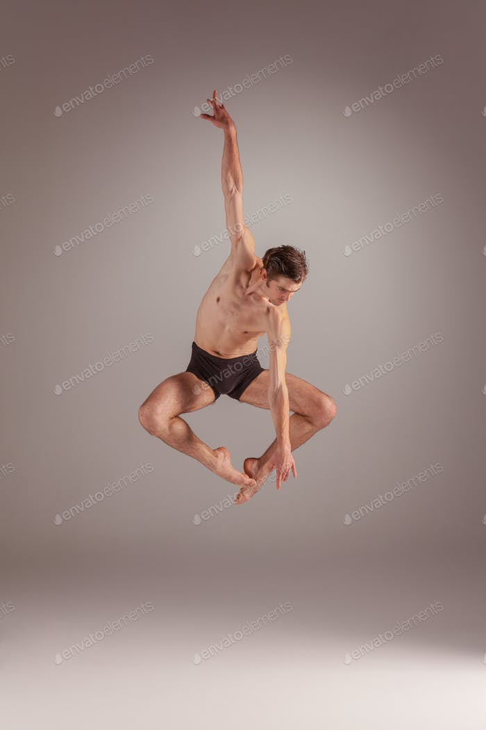The young attractive modern ballet dancer jumping on gray background