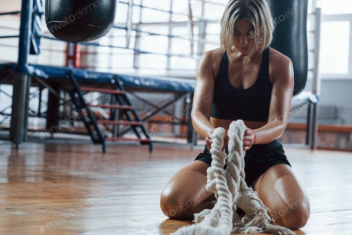Pause machen. Blonde Sport Frau haben Übung mit Seilen in der Turnhalle. Starke Weibchen