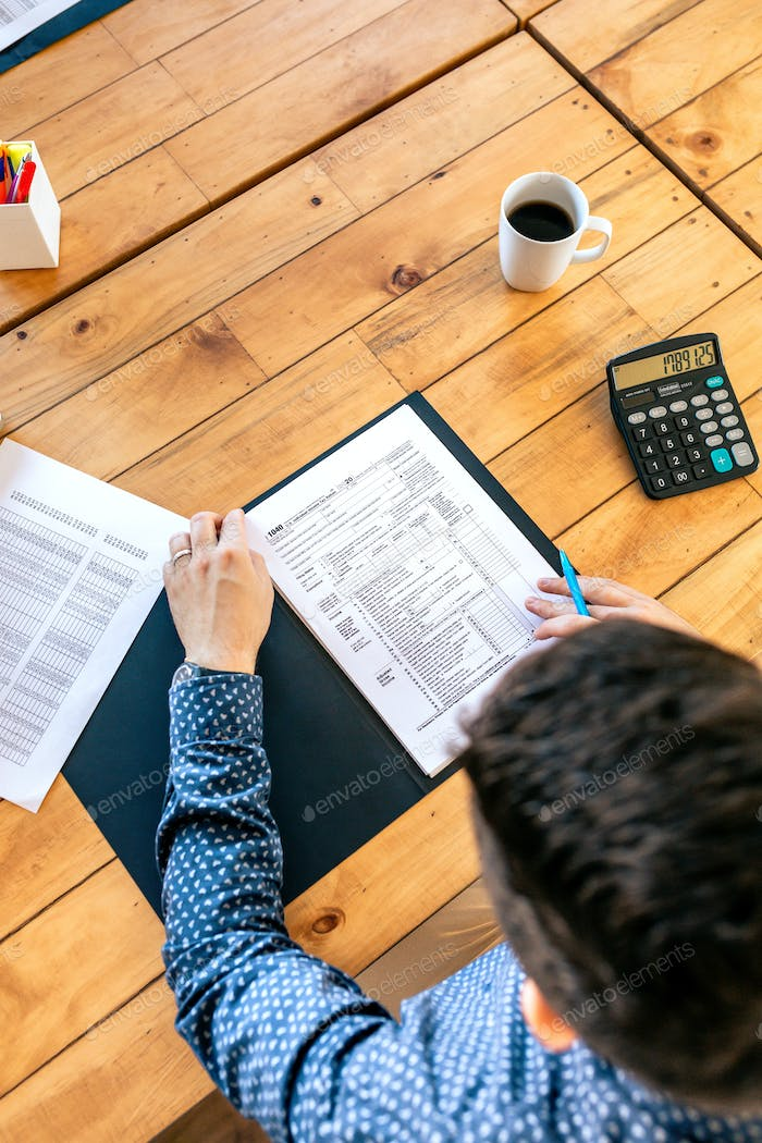 Unrecognizable male taxpayer filling in tax form