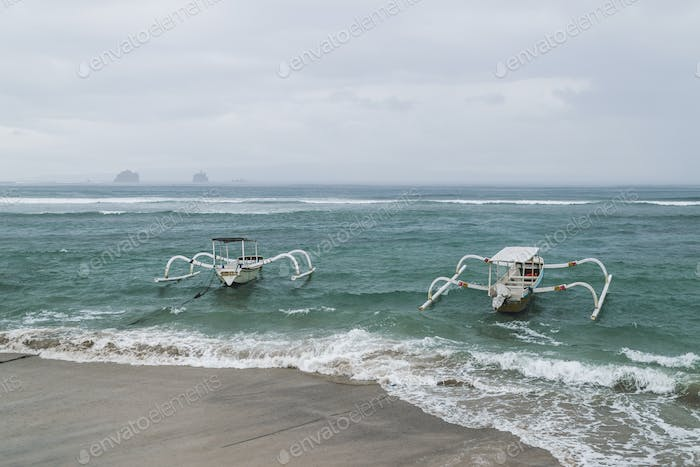 Two traditional Bali fishing boats on big waves in storm and raining. Candidasa beach