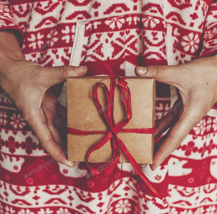 child in red pajamas holding in hands rustic present box with red ribbon