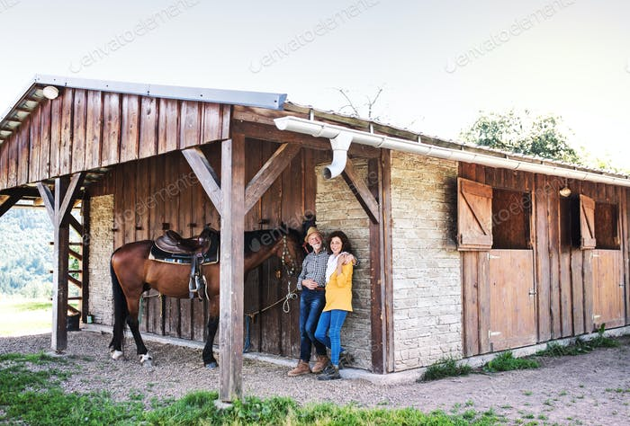 A senior couple with a horse standing in front of a stable.