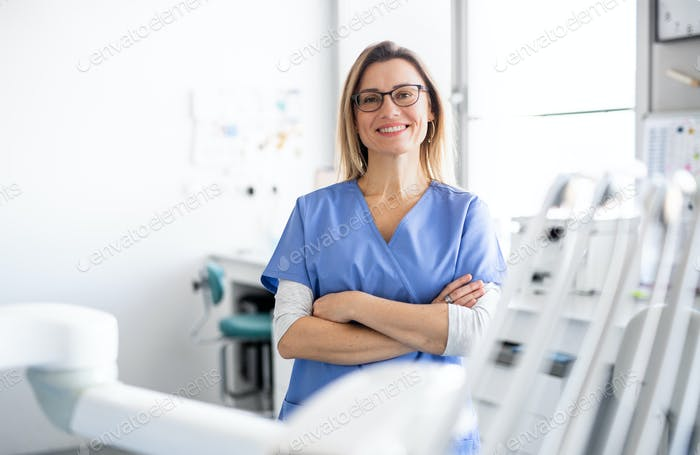 A portrait of dental assistant in modern dental surgery, looking at camera