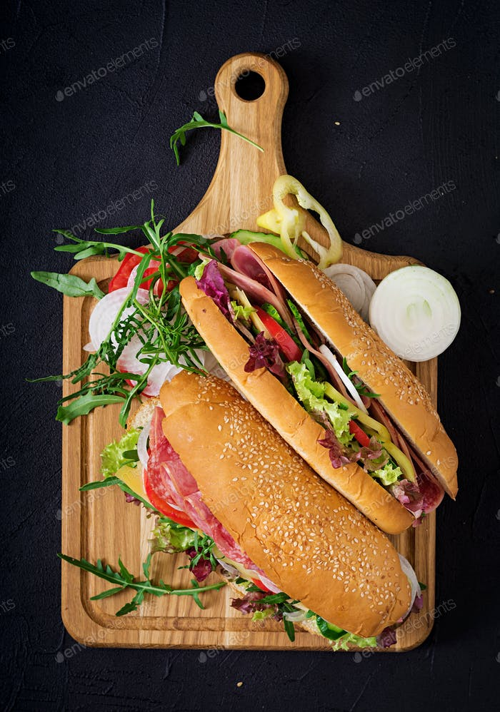 Big sandwich with ham, salami, tomato, cucumber and herbs. Flat lay. Top view