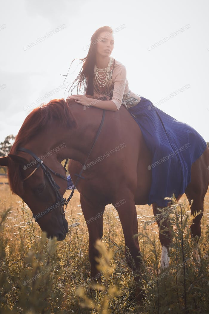 Woman in long blue scirt sitting on brown horse.