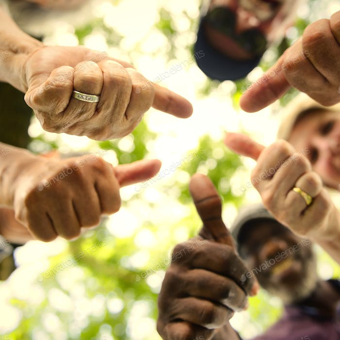 Group of senior friends outdoors thumbs up positivity concept