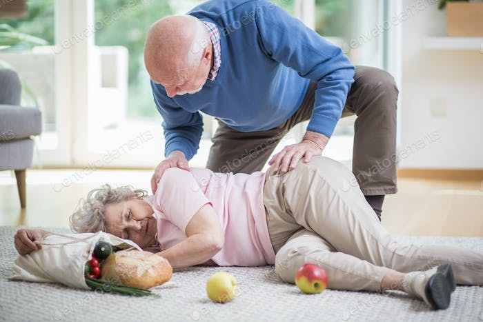 Senior woman lying on the floor of her apartment, and her husband helping her to get up