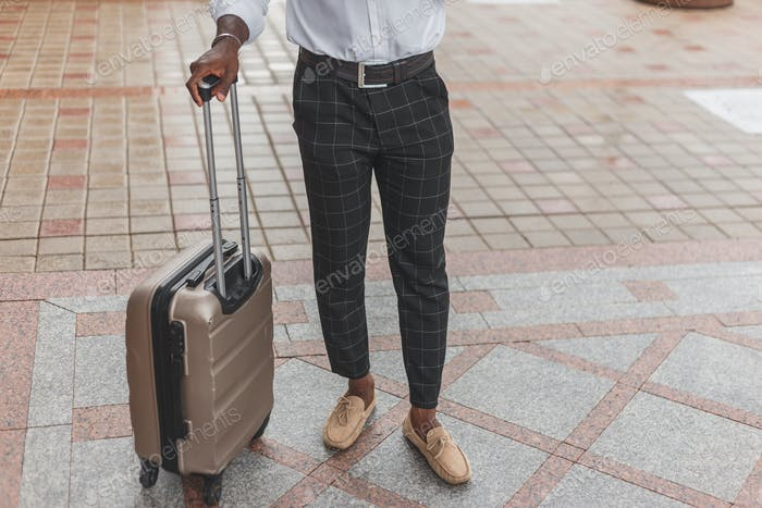 Stilvoll gekleideter schwarzer Kerl mit Gepäck stehend im Freien
