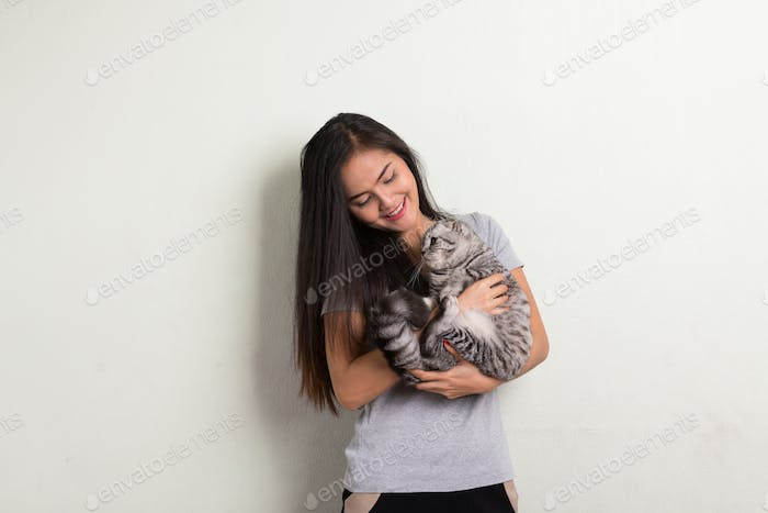 Thumbnail for Young happy beautiful Asian woman smiling while holding cute cat