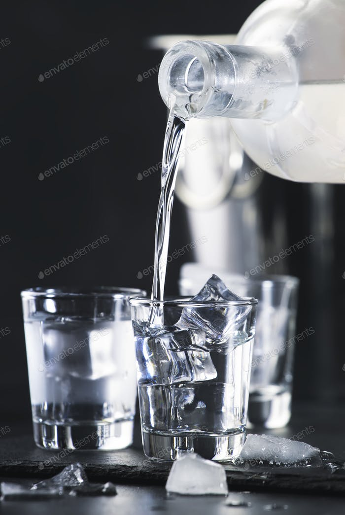 Vodka in shot glasses pouring out of the bottle