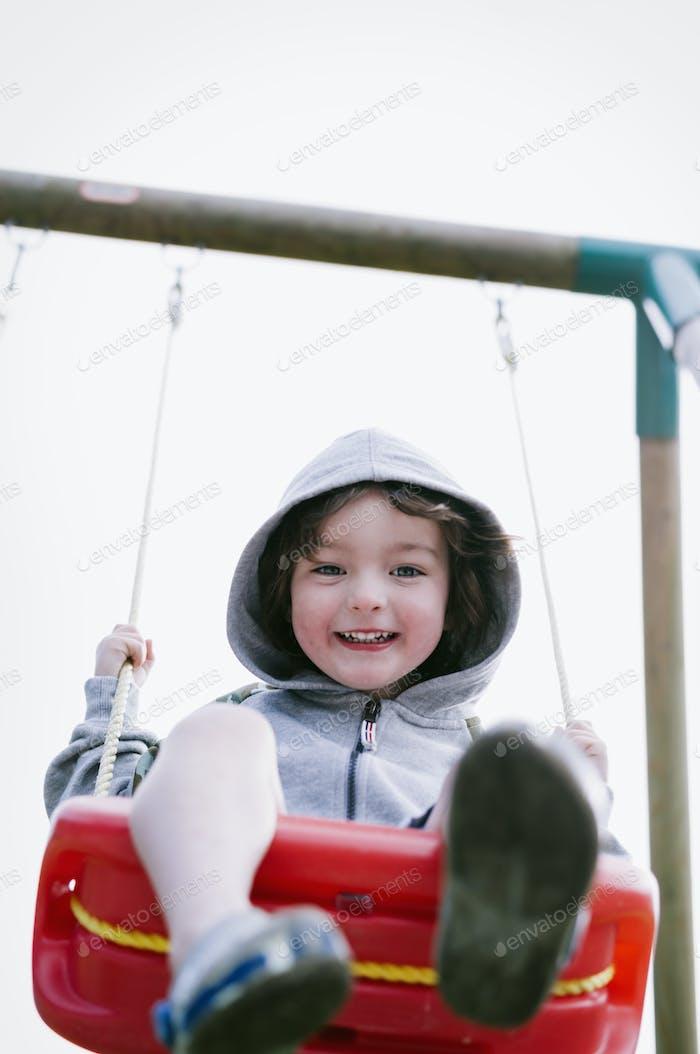 A boy in a hooded fleece, sitting on a swing