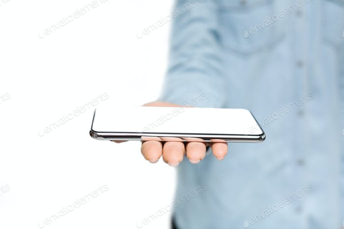 Woman holding modern smartphone with blank screen on open palm