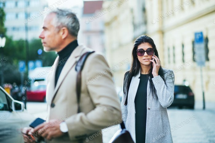 Man and woman business partners walking outdoors in city of Prague.