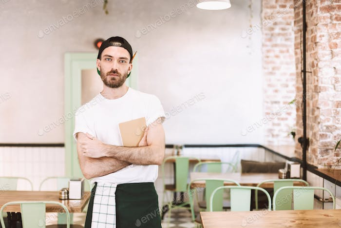 Young waiter in cap t-shirt and apron standing with notepad in hands thoughtfully looking in camera