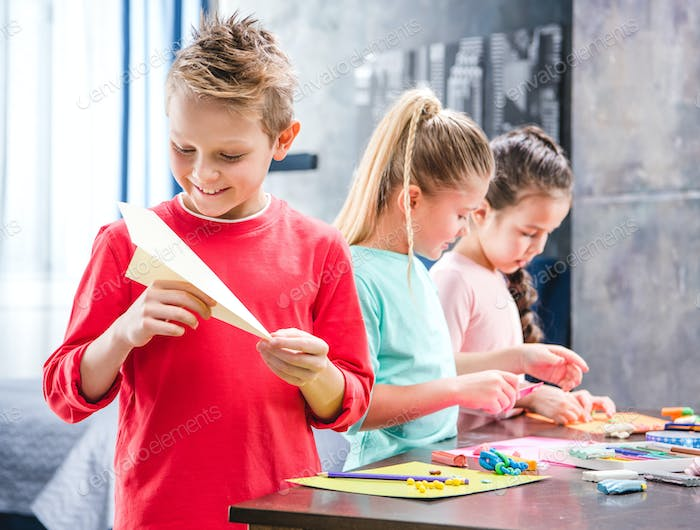 Kid playing with paper plane, schoolchildren molding colorful plasticine