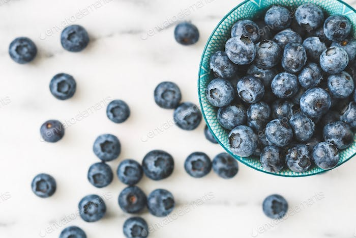 Top view of a blue bowl with fresh ripe blueberry
