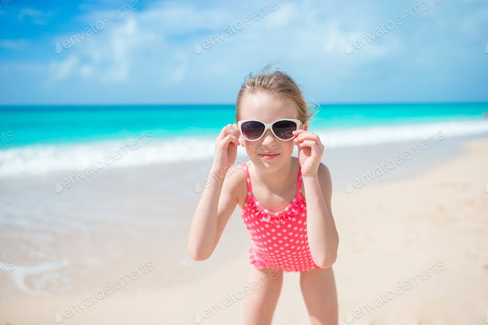 Beautiful little girl in dress at beach having fun