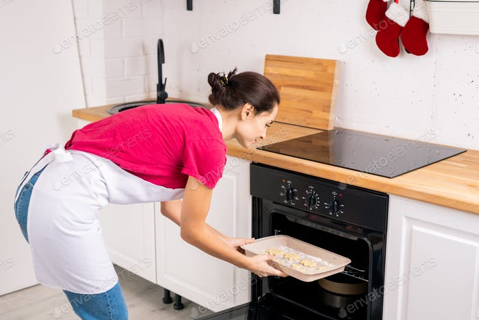 Young housewife in apron putting tray with raw cookies into open oven