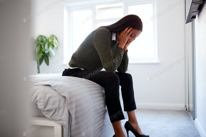 Stressed Businesswoman With Head In Hands Sitting On Edge Of Bed At Home