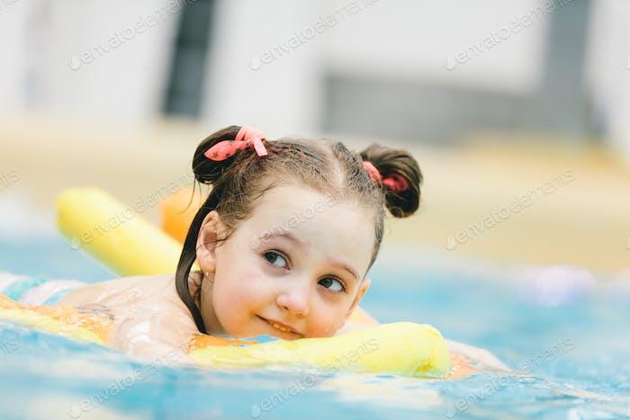 Kleines Mädchen schwimmen mit einer gelben Nudel in einem Pool.
