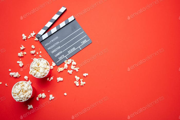Clapperboard and pop corn on red color background, top view