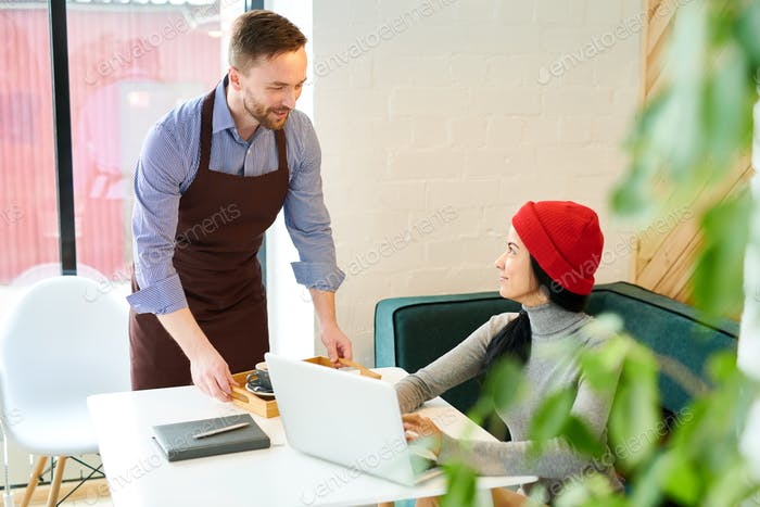 Waiter Serving Young Woman in Cafe