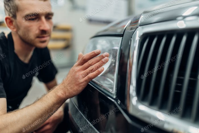 Polishing of car headlight on carwash service