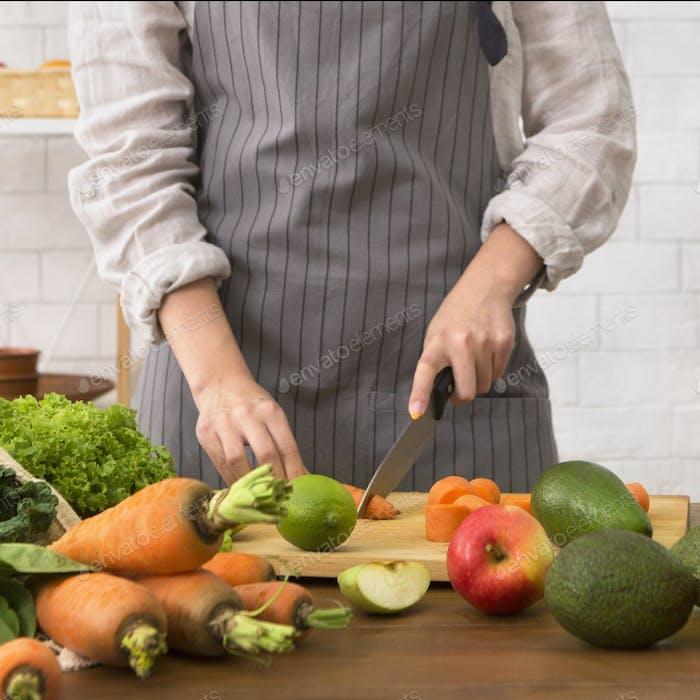Unerkennbare Frau, die leckere Obst- und Gemüsesalat zubereitet